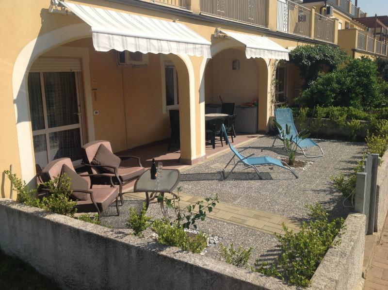 Outdoor living area with dining table, sun loungers, arm chairs and awnings