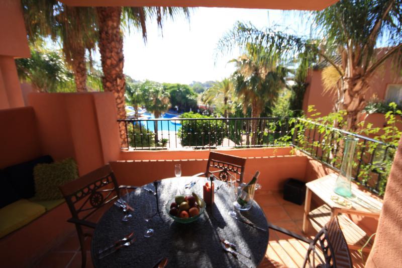 terraza con vistas a la piscina y jardín comedor para seis sol y sombra