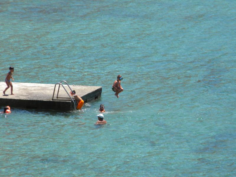 Children jumping off the jetty in Kini