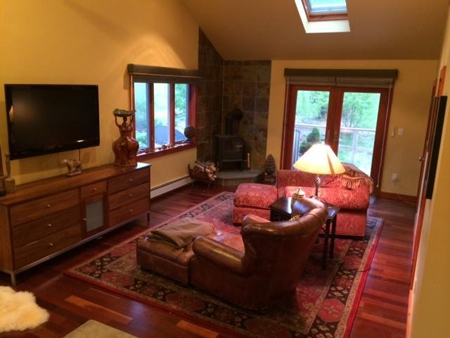 master bedroom sitting area, vaulted ceiling, with lg HDTV and woodstove