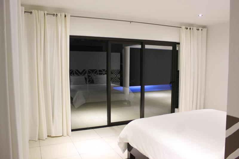 Master bedroom with pool view at night