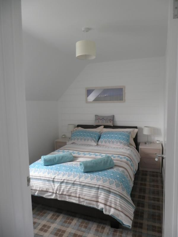 Double bedroom with walk-in wardrobe and TV