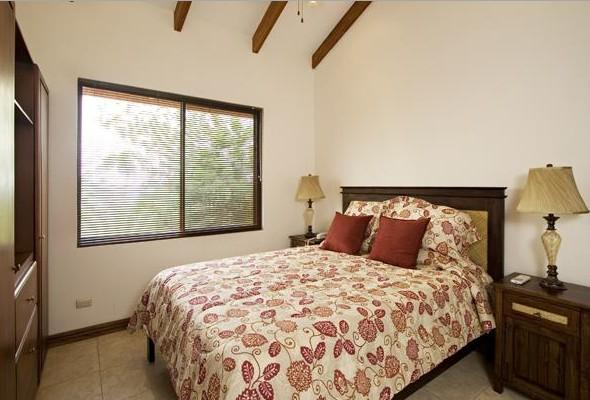 Guest bedroom with queen-size bed, private bath, TV, and ocean view
