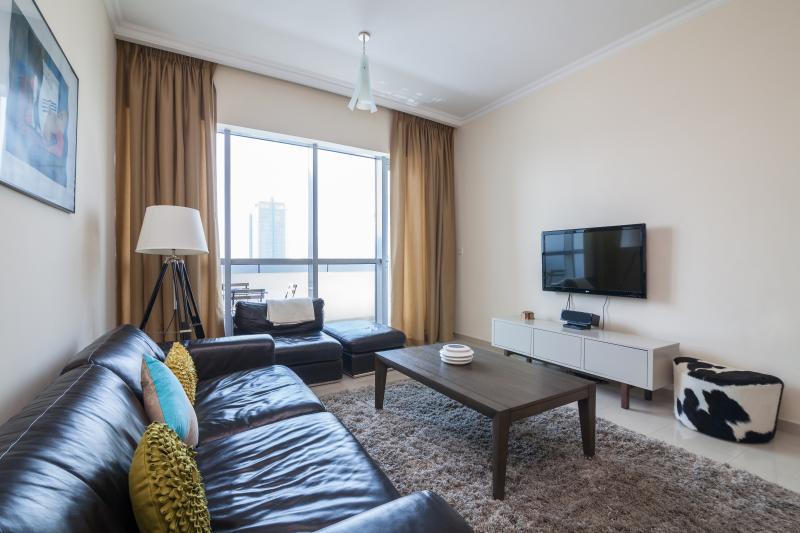 Sala de estar com sofá, TV, ligação para iPod, leitor de DVD e portas deslizantes, levando para a varanda.