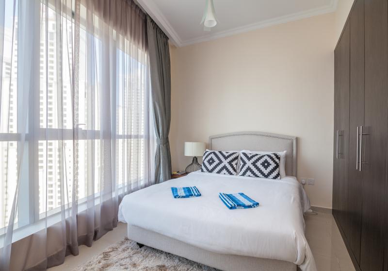 Segundo quarto com cama king size e varanda privada.