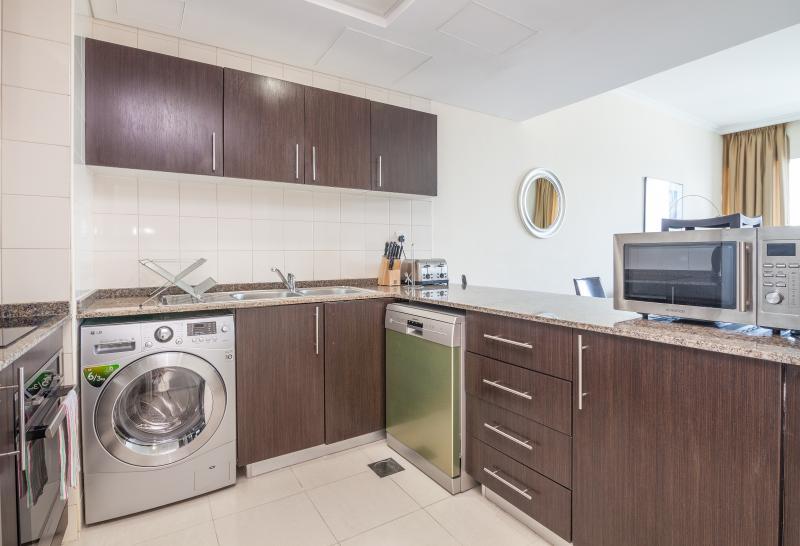 Cozinha totalmente equipada com frigorífico, máquina de lavar e secar roupa, máquina de lavar louça, forno, fogão e microondas...