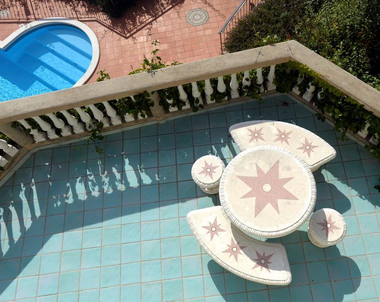 Regardant vers le bas depuis le balcon au 3e étage sur la terrasse et la piscine principale