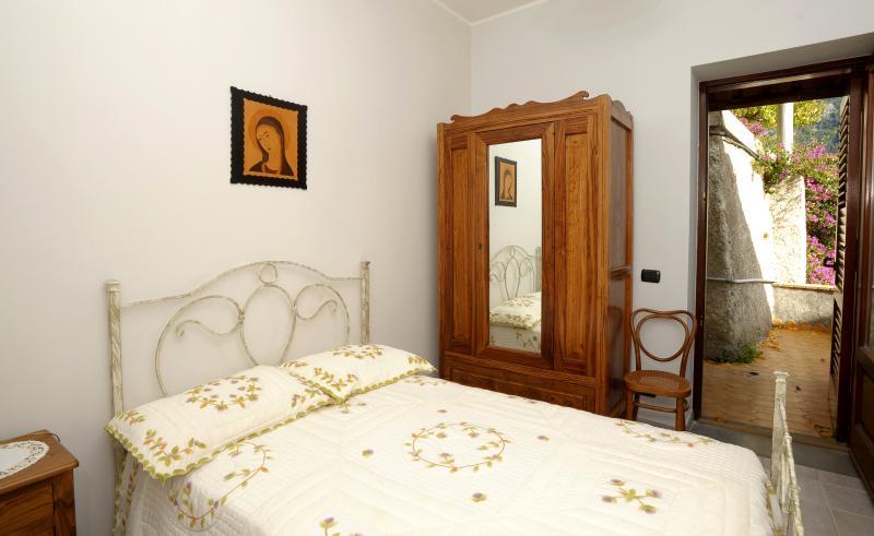 Chambre à coucher avec lit français (surdimensionné unique), et une petite terrasse avec vue partielle sur la mer