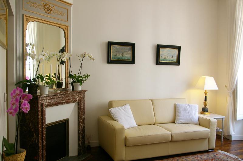 O sofá-cama de couro real junto à lareira em mármore