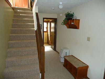 Stairway to downstairs and hallway to full bath, 2 bedrooms and laundry room.