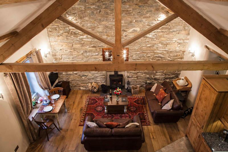 Open plan living room / kitchen with exposed beams and stonework