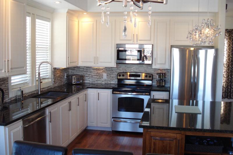 Cocina totalmente equipada con gabinetes de encargo, encimeras de granito y electrodomésticos de acero inoxidables