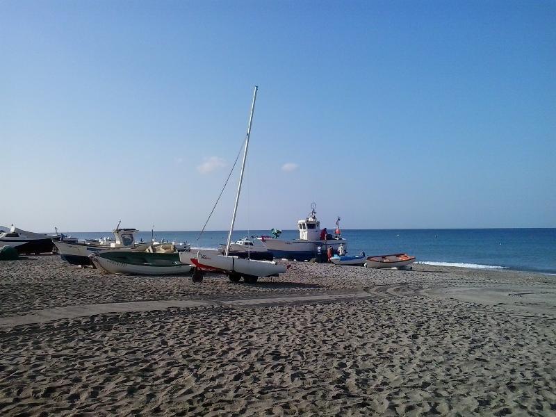 imagen parcial de la playa  a levante  1ª hora de la mañana ,al fondo vista parcial  flota pesquera