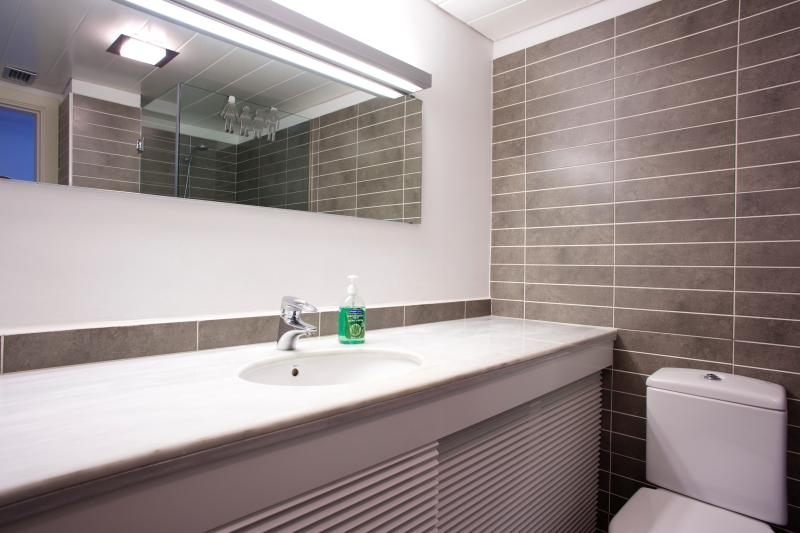 Bathroom with washing machine and dryer under the sink. Soap for hands is provided.