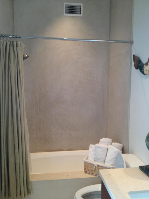 Fresh & Clean Bathroom has contemporary style. Cement type plaster around shower/tub