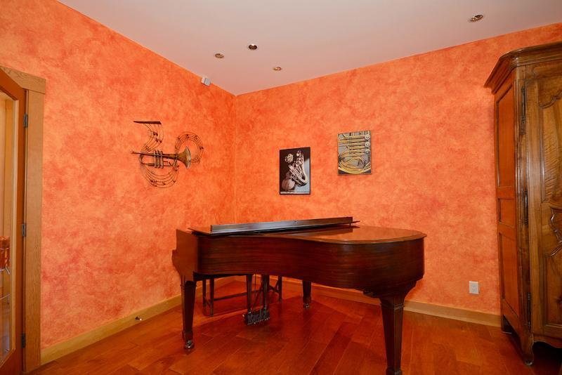 Living room features a baby grand piano