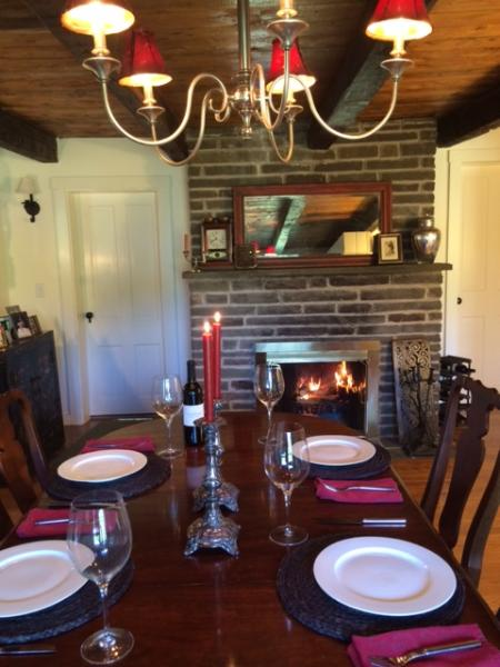 dinner by the stone fireplace with original wood beams
