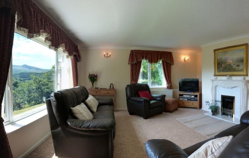 Un atractivo y acogedor salón con un gran ventanal