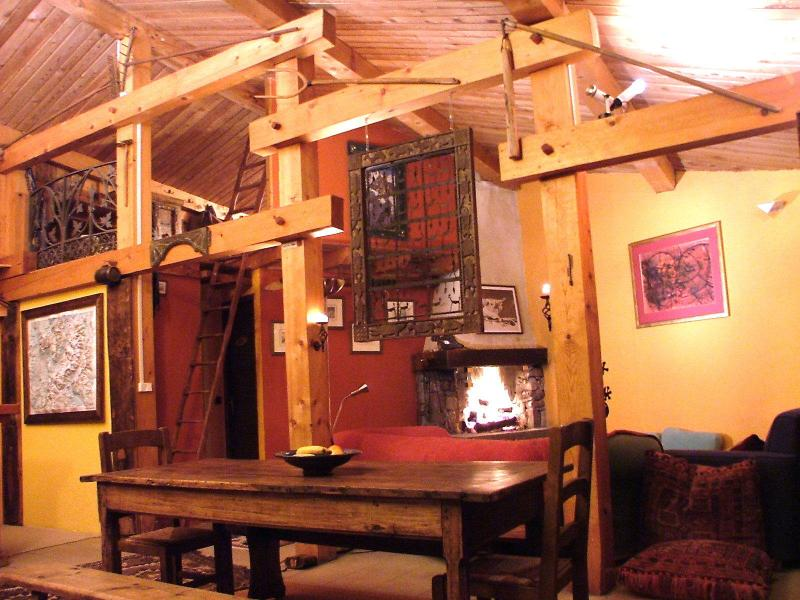 High ceilings, warm open plan lounge/dining area and large open log fire.  Note step ladder to mezz.