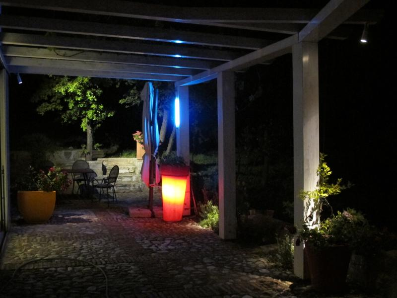 Night-time view of the lit terrace and seating area