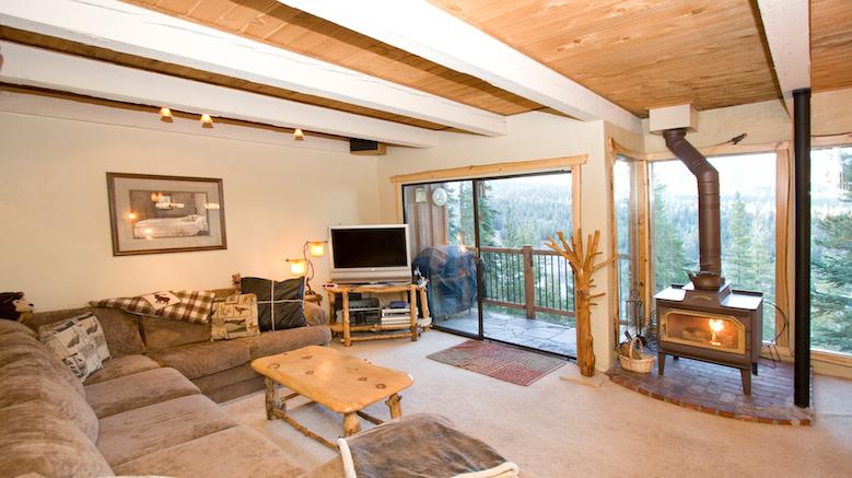 Timber Ridge #45 Living Area With A Wood Burning Fireplace and Floor To Ceiling Windows