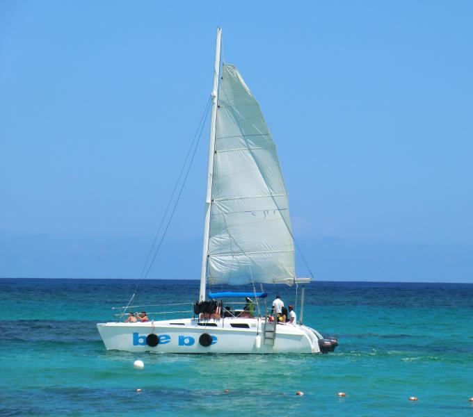 Watch or participate in a catamaran excursion from the beach