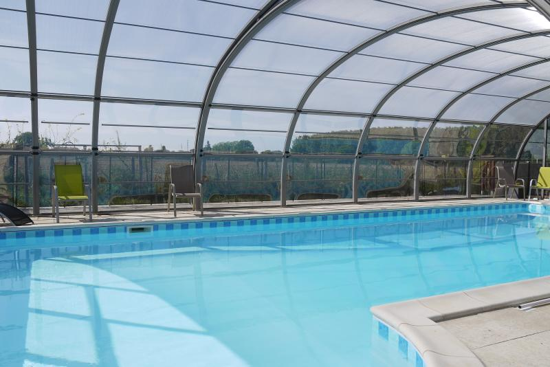 Relax by the heated swimming pool. All the sides of the cover lift up to provide an open air pool. S