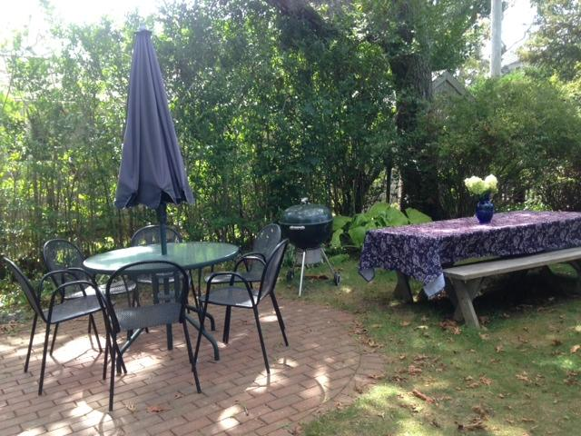 Outside patio, charcoal grill, and tables