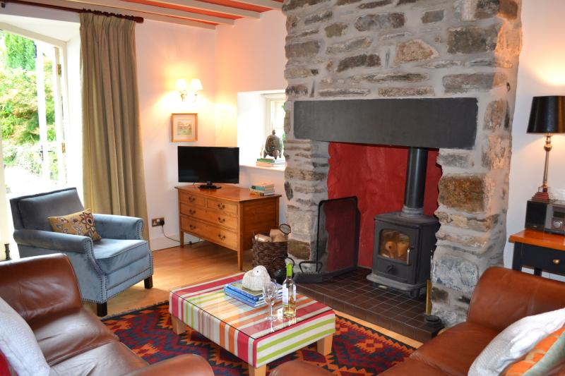 Living area with beamed ceiling & inglenook fireplace with wood burning stove.