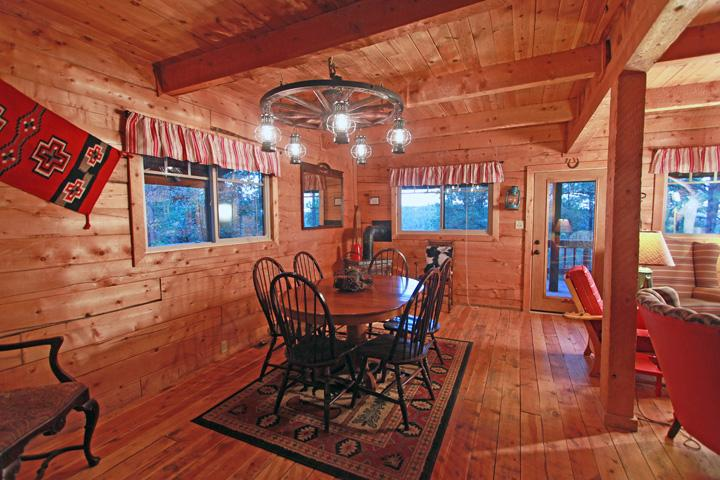 Dining under the Authentic Wagon Wheel Chandelier, Gas Log Stove Fireplace is in the corner
