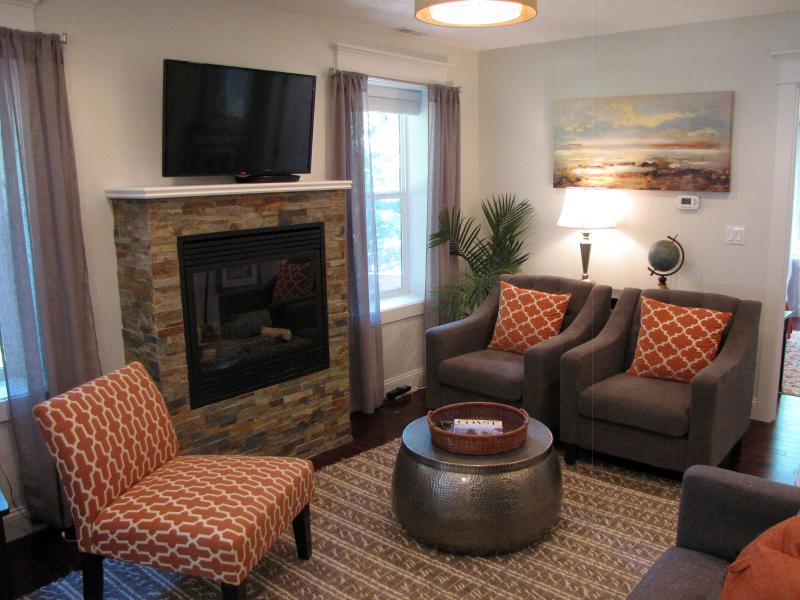 The well-appointed living space with comfy chairs, large windows, and fireplace.