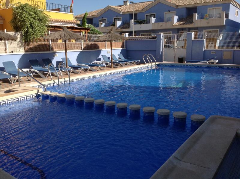 Magnífica piscina con hermosas tumbonas y sombrillas.