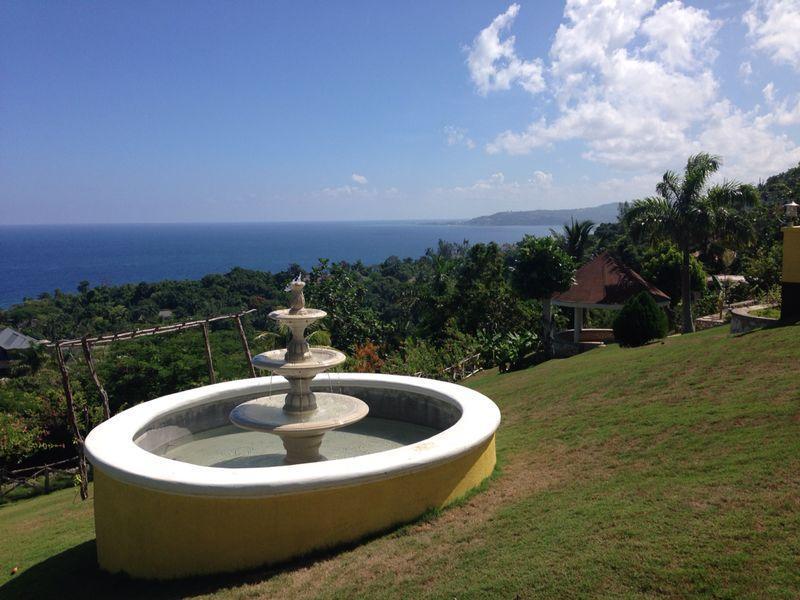 Garden view of water fountain and gazebo overlooking Caribbean Sea