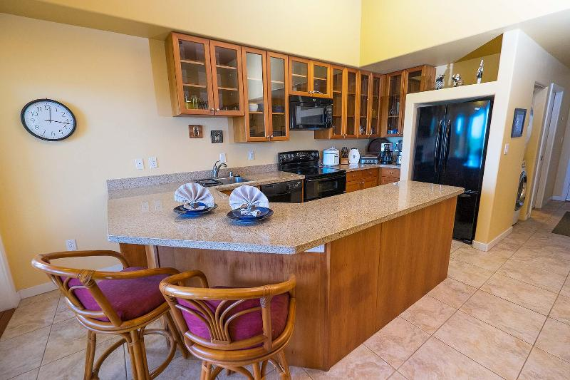 Kitchen features custom glass panel cherry wood cabinets and granite countertops