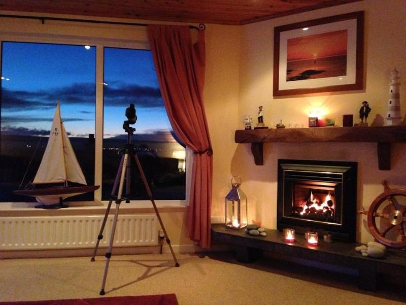 Cosy lounge upstairs with views of sun setting over the sea