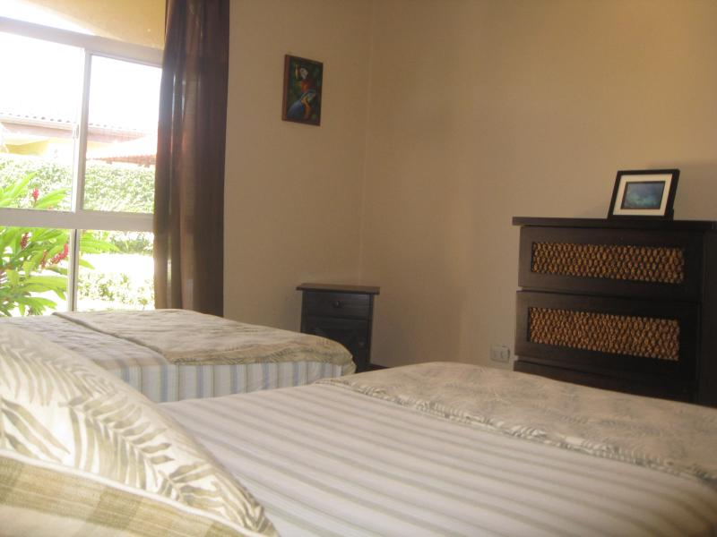Guest room with two single beds that has a view to the pool area.