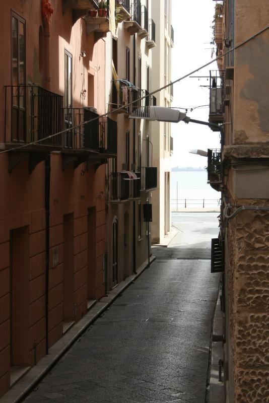 Balcone che si affaccia dalla camera con caratteristica Via del centro e con sfondo il mare.