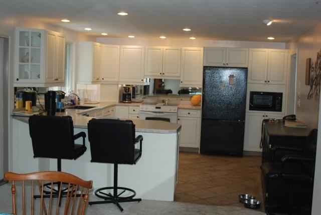 Fully stocked and applianced kitchen with custom wine cooler and breakfast bar