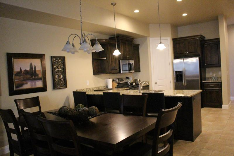 Open floor plan, large table with seating for 8, 4 bar stools, stainless steel appl, granite, pantry