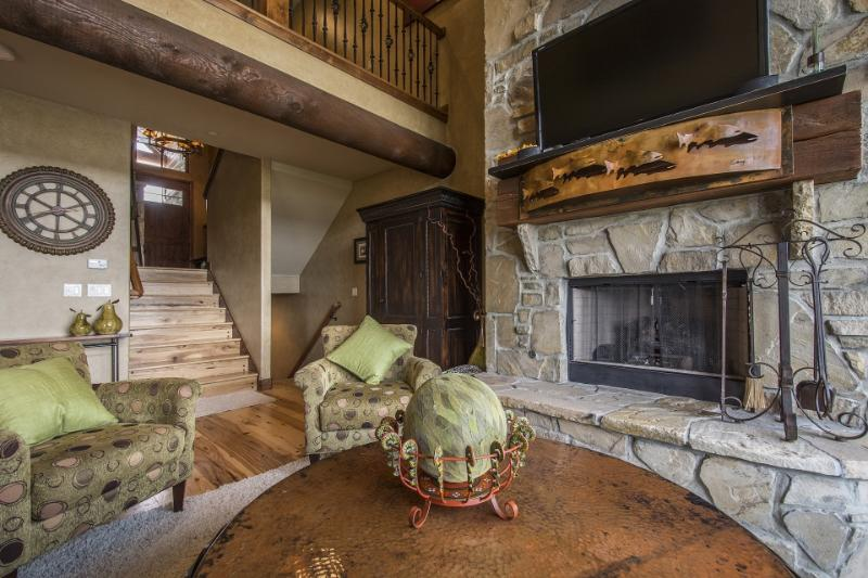Dramatic Floor to Ceiling Stone Fireplace with Custom Mantle