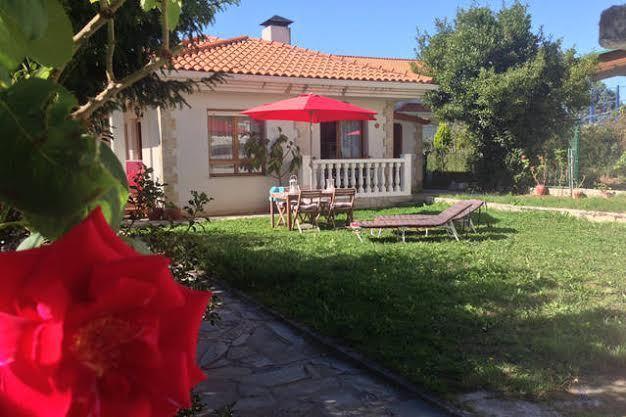Imagen de la fachada con el jardín y mobiliario para difrutar al aire libre.