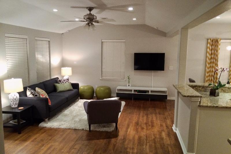 Vista del soggiorno con TV a schermo piatto; flussi per sala da pranzo e cucina.