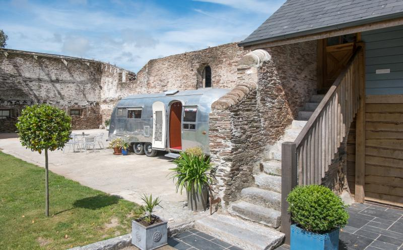 Historic courtyard with steps leading up to Swallows' Flight and Airstream caravan