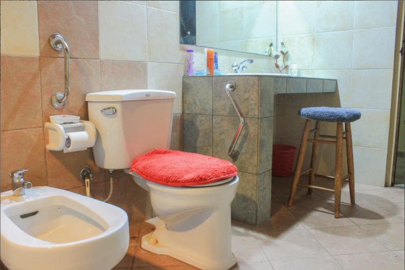 View of toilet, with disable-friendly fixtures