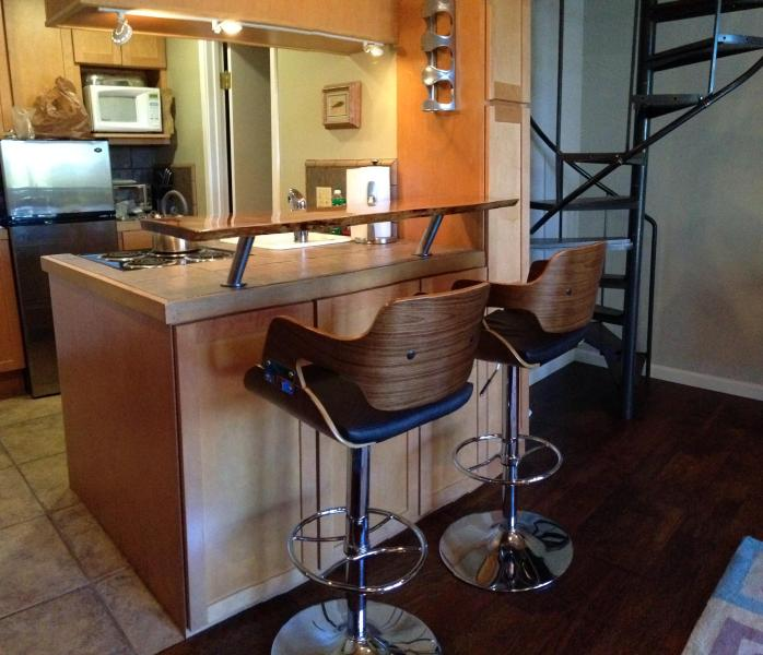 Walnut dining stools on floating live edge counter bartop