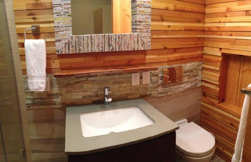 Wall mount toilet, ledge stone backsplash, buddha stone counter top and hans grohe faucet