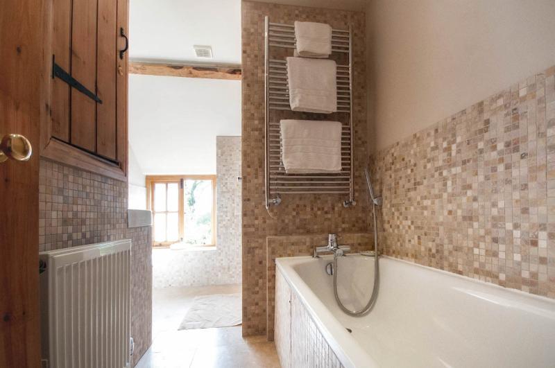 Modern bathroom with bath, large walk in shower, basin, toilet and heated towel rail