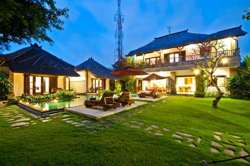 La casa de huéspedes ubicada en una propiedad grande con mucho verde.