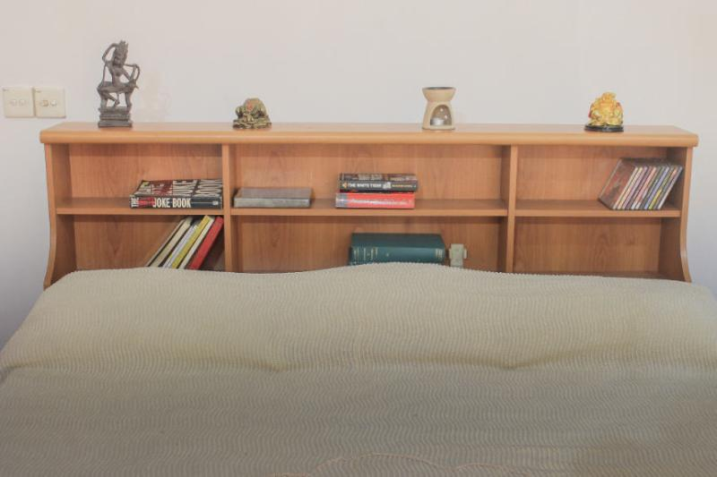 Bookshelf by the bed, with short reads and music provided