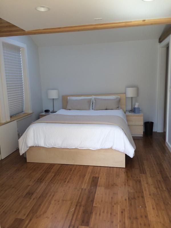 Bedroom with bamboo floors, queen bed, and lots of comfy bedding.